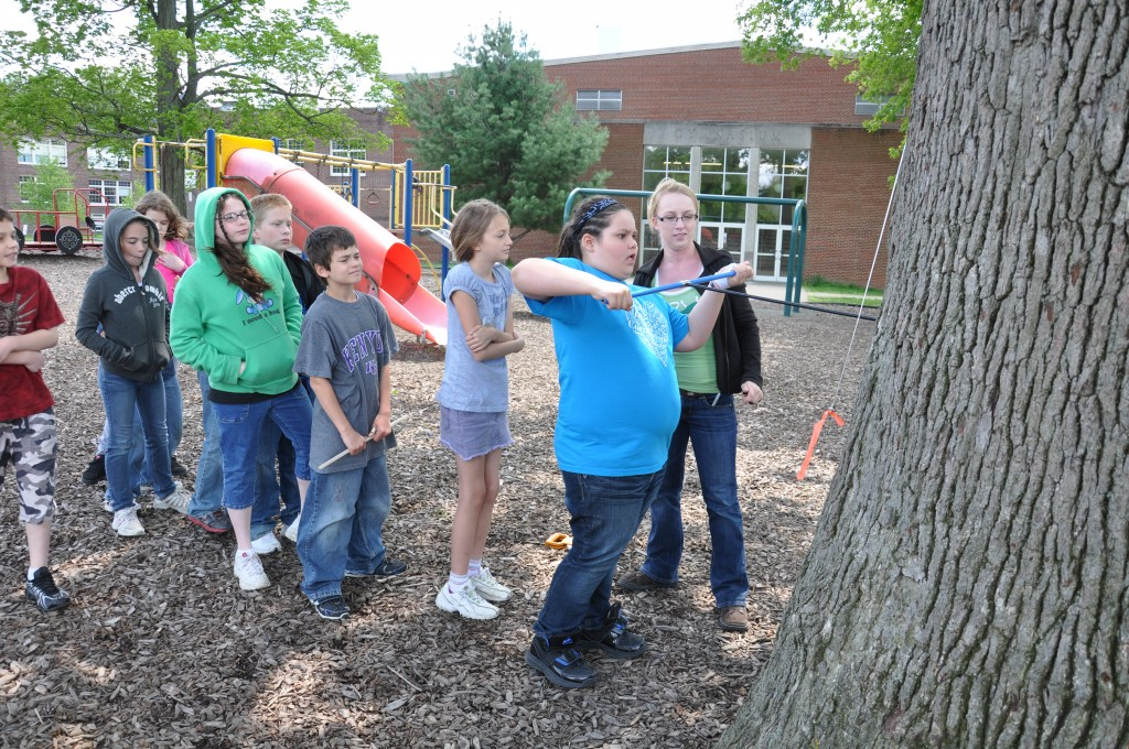 Sarah Appleton '11 helps Cornerstone students core a tree