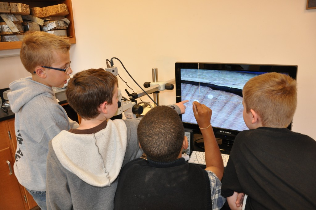 Cornerstone students look at a tree core under the microscope on a monitor display