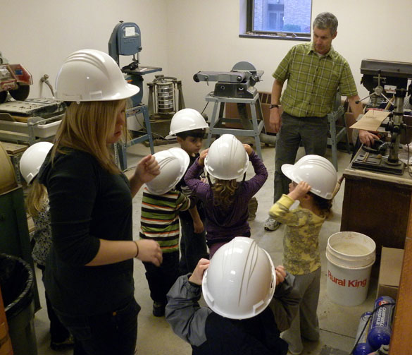 Children wearing hardhats in the preparation area (also the saw room in Scovel Hall)