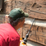 Image - Coring the wall of a log cabin with a drill