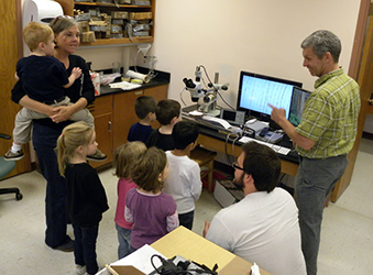 Dr. Wiles shows The College of Wooster Nursery School children cores under the microscope in the lab annex